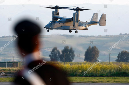 An Italian Carabinieri officer looks on as an MV-22 Osprey vertical take off and lift aircraft lands with on board US General Carter Ham, Commander of the United States military mission in Libya, in the Sigonella airbase, Sicily