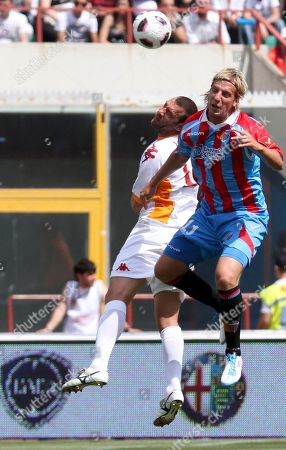 Catania's Maximiliano Lopez, of Argentina, right, jump for the ball with AS Roma's Simone Loria, during a Serie A soccer match at Catania's Angelo Massimino stadium, Italy