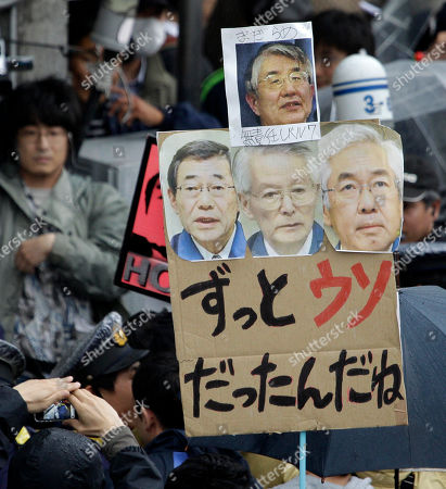 "Anti-nuclear protesters, one holding a placard bearing images of Tokyo Electric Power Co. (TEPCO) executives, march in downtown Tokyo . Images from left are: TEPCO President Masataka Shimizu, Chairman Tsunehisa Katsumata and Vice President Sakae Muto. At top is Nuclear Safety Commission Chief Haruki Madarame. The words said:""(You) have being telling lies for long time"