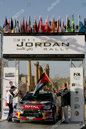 Prince Faisal,Sebastian Ogie Jordan's Prince Faisal, right, holds the start flag for Citroen driver Sebastian Ogier at the opening ceremony of the 4th round of the FIA World Rally Championship, at the ancient city of Jerash, 55 kilometres (32 miles) north Amman, Jordan, Thursday, April, 14, 2011