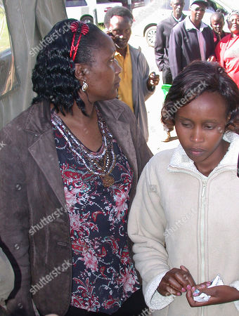 Stock Photo of Triza Kamau, right, the wife of the Kenyan Olympic marathon champion Sammy Wanjiru with a relative at their home in Nyahururu Kenya . Kenyan Olympic marathon champion Sammy Wanjiru died Monday in a fall from a balcony after a domestic dispute involving his wife and another woman, police said