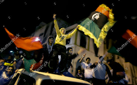 Youths on the roofs of vehicles waving pre-Gadhafi era Libyan flags now used by the opposition, ride through the streets at night in Benghazi, Libya . In a sign the international airstrikes may be eroding Gadhafi's resilience, his government is trying to hold talks with the U.S., Britain and France in hopes of ending the air campaign, according to Abdul-Ati al-Obeidi, a former Libyan prime minister who has served as a Gadhafi envoy during the crisis