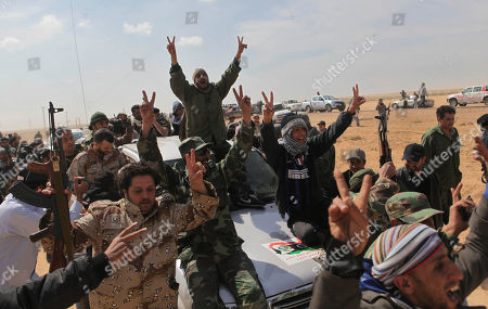 Stock Photo of Libyan rebels shout slogans atop the vehicle of General Abdel-Fattah Younis, former interior minister in the Gadhafi regime who defected early, who pays a visit to the front line near Brega, Libya