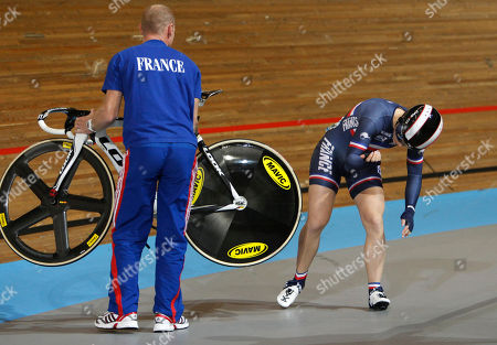 The coach of the French team helps Sandie Clair get up after she slipped when competing in the women's sprint 1/16 finals during the Track Cycling World Championships in Apeldoorn, central Netherlands