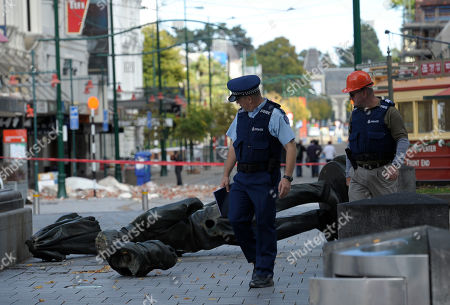 Two police officers look down at the fallen statue of the city's founder, Irishman John Robert Godley in Christchurch, New Zealand. Christchurch Major Bob Parker said that a handwritten parchment in a bottle and a sealed copper cylinder believed to contain documents were discovered inside the statue of the city's founder