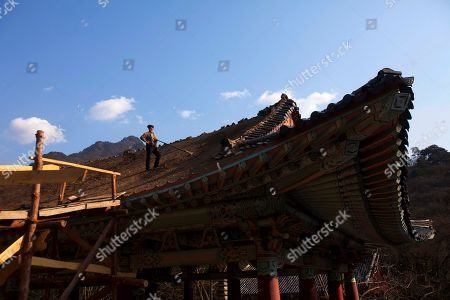 A North Korean man rebuilds the traditional rooftop of a structure at the Pohyon Temple, at the foot of Mount Myohyang, North Korea. It's hard to imagine a North Korea without Kim Jong Il, who led the nation for 17 years until his death on Dec. 17. His death marks the end of an era for North Korea, which has known only two leaders: Kim and his father, Kim Il Sung. Already, a new era has begun under the leadership of his young son, Kim Jong Un. Still, Kim Jong Il's presence is felt in every frame of a series of images made by Associated Press photographer David Guttenfelder. During the last months of Kim's life, Guttenfelder, along with AP Korea Bureau Chief Jean H. Lee, made several trips to North Korea