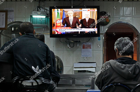 People in a restaurant watch Portuguese interim Prime Minister Jose Socrates, left on screen, with Finance Minister Fernando Teixeira dos Santos, as they address the country live on television, to announce the results of negotiations on an international financial bailout. Local Portuguese officials and delegates from the International Monetary Fund, the European Central Bank and the European Commission have conducted confidential consultations in Lisbon for about three weeks since Portugal asked for help last month