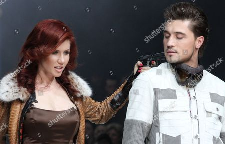 Anna Chapman On, Anna Chapman, left, who was deported from the U.S. on charges of espionage, and Russian pop singer and Eurovision 2008 contest winner Dima Bilan display a creation by Russian designers Shiyan & Rudkovskaya during a Fashion Week in Moscow, Russia. A year and a half after the biggest spy swap since the Cold War, its Russian protagonists completely vanished in the 12-million city of Moscow, leaving no trace of their past, except for compulsive socialite Anna Chaman