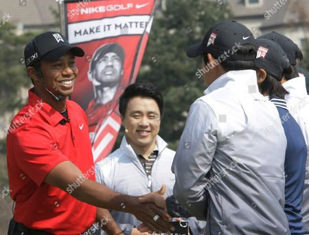 Stock Photo of Tiger Woods U.S. golfer Tiger Woods, left, shakes hands with South Korean young golfers during a golf clinic as part of his Asian tour at the Jade Palace Golf Club in Chuncheon, South Korea