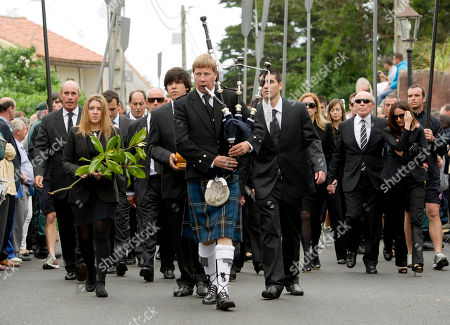 Stock Photo of Seve Ballesteros, Javier Ballesteros, Carmen Ballesteros, Miguel Ballesteros A musician, front, plays the bagpipes as Seve Ballesteros' oldest son, Javier, carries the urn holding the Spanish golfer's ashes, flanked by his sister, Carmen, left, holding flowers and their brother, Miguel, right, in honor of Spanish professional golfer Seve Ballesteros, during his funeral service in Pedrena, Spain, . Ballesteros, 54, a five-time major tournament winner, died last Saturday of from complications of a cancerous brain tumor