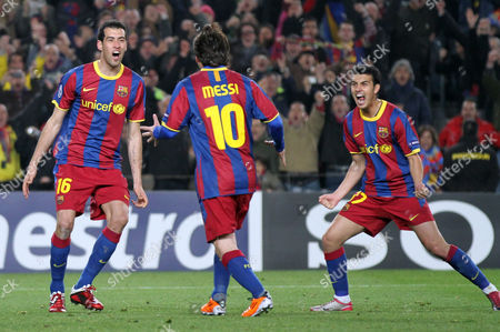 Stock Image of Lionel Messi, Sergio Busquest, Pedro Rodriguez FC Barcelona's Lionel Messi, center, of Argentina celebrates with teammates Sergio Busquest, left, and Pedro Rodriguez after scoring a penalty during a Champions League, round of 16, second leg soccer match at the Nou Camp, in Barcelona, Spain