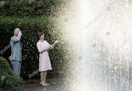 Prince Charles views a water feature with Duchess of Northumberland  in the gardens  at  Alnwick Castle
