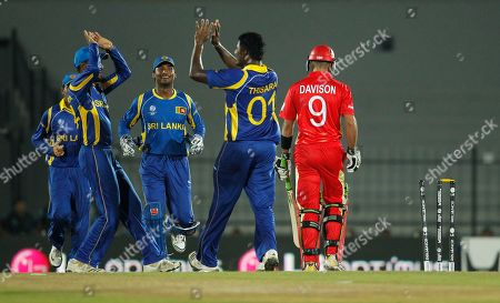 Canada's batsman John Davison, in red, walks back to the pavilion after being dismissed as Sri Lankan team members congratulate their bowler Thisara Perera, second left, during the ICC Cricket World Cup match between Sri Lanka and Canada in Hambantota, Sri Lanka