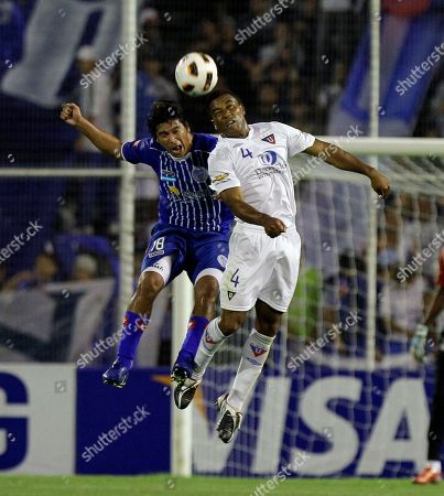 Ruben Ramirez of Argentina's Godoy Cruz, left, fights for the ball with Hernan De La Cruz of Ecuador's Liga Deportiva Universitaria de Quito, during a Copa Libertadores soccer match in Mendoza, Argentina