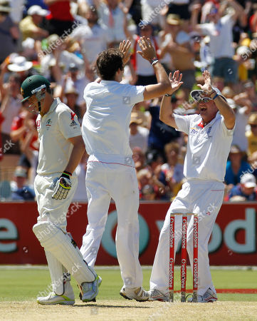 Andrew Strauss, Steve Finn, Marcus North England's captain Andrew Strauss, right, celebrates with teammate Steve Finn as Australia's Marcus North, left, walks off during the first day of their second Ashes cricket test in Adelaide, Australia