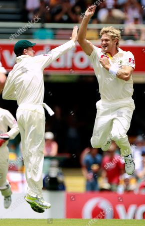 Australia's Marcus North, left, congratulates teammate Shane Watson after England's Jonathan Trott was bowled by Watson for 29 runs during the first day of the first Ashes cricket test in Brisbane, Australia
