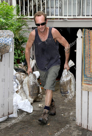 Kevin Lewis helps clear debris from the home of a friend in the flooded suburbs in Brisbane, Australia, . Parts of Brisbane reopened as deadly floodwaters that had swamped entire neighborhoods recede, revealing streets and thousands of homes covered in a thick layer of putrid sludge