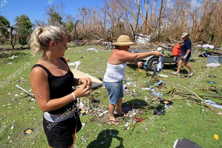 Stock Photo of Kaylee Flegler, left, and her mother Kristina sift through debris looking for their belongings along with Pete Murray in Tully Heads, Australia, after Cyclone Yasi brought heavy rain and howling winds gusting to 186 mph (300 kph). Yasi ripped across the coast near Cairns on Wednesday night, tearing apart dozens of homes and damaging hundreds more, cutting power to tens of thousands of people and flattening millions of dollars worth of crops