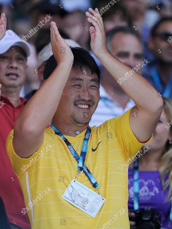 Jian Shan Coach and husband of China's Li Na, Jiang Shan applauds his wife as she speaks to the crowd following her win over Denmark's Caroline Wozniacki in their women's semifinal at the Australian Open tennis championships in Melbourne, Australia