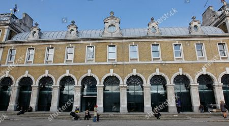 Stock Image of Pedestrians stroll past the 19th century Old Billingsgate Fish Market designed by Sir Horace Jones and renovated in 1988 by architect Richard Rogers alongside the River Thames in London, . The building has been earmarked by France as a hospitality venue for the 2012 London Olympic Games