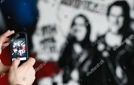 A tourists takes a photo with a smart phone, of a newly unveiled graffiti portrait of Prince William and Kate Middleton by street artist Rich Simmons, in London, . It is probably not quite the wedding portrait Prince William and Kate Middleton had in mind. The soon-to-be-married couple have been made over as punk 'royalty' by an artist who has transformed them into the King and Queen of rockers, Sid Vicious and Nancy Spungen, and it was a Prince's Trust grant that helped artist Rich Simmons hone his skills which led to the punky version of the pair