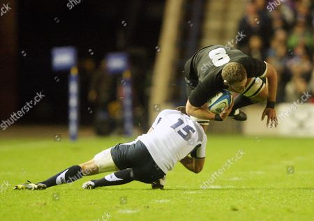 New Zealand's Kieran Read, right, is tackled by Scotland's Hugo Southwell, left, during the international rugby match at Murrayfield, Edinburgh, Scotland