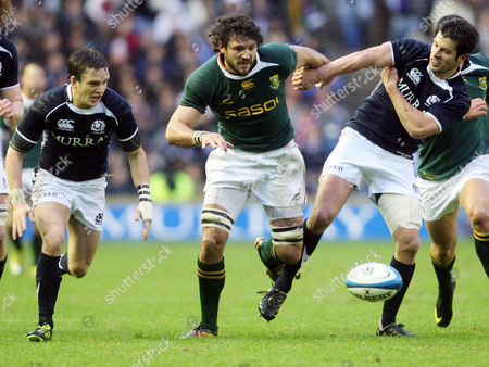 South Africa's Ryan Kankowski, center, is tackled by Scotland's Hugo Southwell, right, and Rory Lawson, left, during the international rugby match at Murrayfield, Edinburgh, Scotland