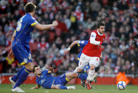 Arsenal's Cesc Fabregas, right, controls the ball past the tackle of Leeds United's Ben Parker during their English FA Cup third round soccer match at Arsenal's Emirates stadium in London . The match ended in a 1-1 draw. (AP Photo/Alastair Grant) NO INTERNET/MOBILE USAGE WITHOUT FOOTBALL ASSOCIATION PREMIER LEAGUE(FAPL)LICENCE. CALL +44