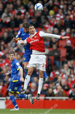 Arsenal's Marouane Chamakh, right front, goes for the ball with Leeds United's Ben Parker during their English FA Cup third round soccer match at Arsenal's Emirates stadium in London Saturday, Jan, 8 2011 . (AP Photo/Alastair Grant) ** NO INTERNET/MOBILE USAGE WITHOUT FOOTBALL ASSOCIATION PREMIER LEAGUE(FAPL)LICENCE. CALL +44