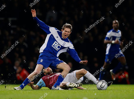 West Ham United's Matthew Upson falls as he vies for the ball with Birmingham City's Alexander Hleb during their English League Cup semi-final soccer match at West Ham's Upton Park Stadium in London, . (AP Photo/Kirsty Wigglesworth) NO INTERNET/MOBILE USAGE WITHOUT FOOTBALL ASSOCIATION PREMIER LEAGUE(FAPL)LICENCE. CALL +44