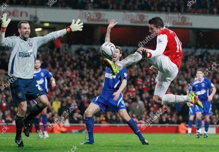 Arsenal's Robin van Persie, right, tries to shoot past Ipswich Town's goalkeeper Marton Fulop, left, during the English League Cup semifinal soccer match between Arsenal and Ipswich Town at the Emirates stadium in London, . (AP Photo/Matt Dunham) NO INTERNET/MOBILE USAGE WITHOUT FOOTBALL ASSOCIATION PREMIER LEAGUE(FAPL)LICENCE. CALL +44