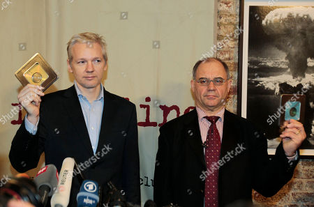 WikiLeaks founder Julian Assange, left, accompanied by former Swiss banker Rudolf Elmer, right, are seen after Elmer handed Assange two CD cases full of files, following a news conference at the Frontline Club in London, . Elmer blew the whistle on the conduct of Julius Baer Bank in the Cayman Islands for which he is set to stand trial in Zurich, Switzerland, on Jan. 19 for breaching Swiss bank secrecy laws. Accompanied by his lawyer Jack Blum, he will reveal more details of alleged abuses in the world of offshore financial centres. As he did back in 2007 he will pass the said documents and information to Wikileaks