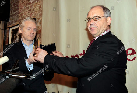 Former Swiss banker by Rudolf Elmer hands two CD cases full of files to WikiLeaks founder Julian Assange, left, following a news conference at the Frontline Club in London, . Elmer blew the whistle on the conduct of Julius Baer Bank in the Cayman Islands for which he is set to stand trial in Zurich, Switzerland, on Jan. 19 for breaching Swiss bank secrecy laws. Accompanied by his lawyer Jack Blum, he will reveal more details of alleged abuses in the world of offshore financial centres. As he did back in 2007 he will pass the said documents and information to Wikileaks