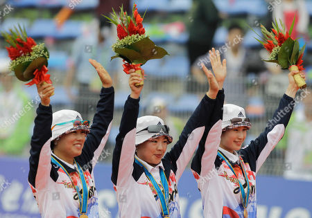 South Korean archers, from left, Joo Hyun-jung, Yun Ok-hee and Ki Bo-bae celebrate after winning the gold medal in the women's archery team final at the Asian Games in Guangzhou, China