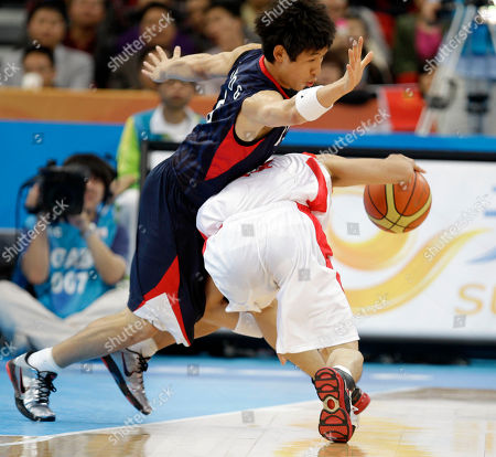 North Korea's Kye Kwang Yu, right, tries to push past South Korea's Yang Dong-geun during their men's basketball match at the Asian Games in Guangzhou, China