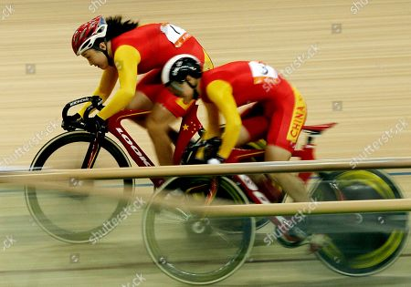 China's Guo Shuang left, races compatriot Lin Junhong to take the gold medal during the finals of the women's sprint cycling event for the Asian Games in Guangzhou, China