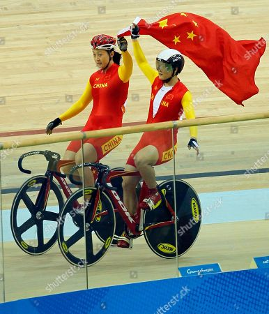 China's Guo Shuang, gold at left and China's Lin Junhong, silver at right, ride with the Chinese national flag to celebrate their win in the women's sprint cycling event at the Asian Games in Guangzhou, China