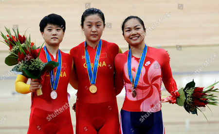 From left China's Lin Junhong, silver, China's Guo Shuang, gold and Hong Kong's Lee Wai Sze, bronze pose for photos after the medal ceremony for the women's sprint cycling event for the Asian Games in Guangzhou, China