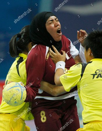 Qatar's Zayadien Abdulla Al Naimi, center, reacts as she is being fouled by Taiwan's Hung Tzu Chin, right, and Tsai Tzu Hsuan, left, during their handball match at the 16th Asian Games in Guangzhou, China