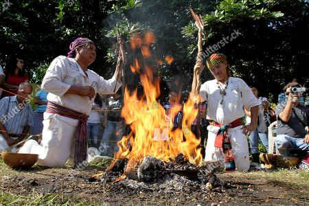 Mayan priests Tata Carlos Cuyuth, left, and Tata Juan lead a sacred fire ceremony marking the 79th anniversary of the 1932 massacre of thousands of Indians by the armed forces during the dictatorship of General Maximiliano Hernandez Martinez in Izalco, El Salvador