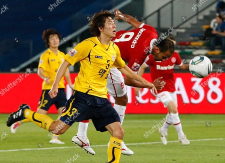 Brazil's SC Internacional do Porto Alegre soccer player, background, heads fights the ball against South Korea's Seongnam Ilhwa Chunma soccer player Yun Young Sun, foreground, during their third place of FIFA Club World Cup soccer match, at Zayed sport city stadium, in Abu Dhabi, UAE