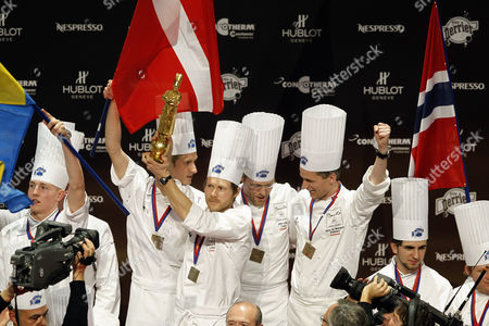 """Rasmus Kofoed Rasmus Kofoed of Denmark, center, holds his trophy as he celebrates on the podium with his teammates after winning the """"Bocuse d'Or"""" (Golden Bocuse) trophy, at the 13th World Cuisine contest, in Lyon, central France, . The contest, a sort of world cup of the cuisine, was started in 1987 by Lyon chef Paul Bocuse to reward young international culinary talents"""