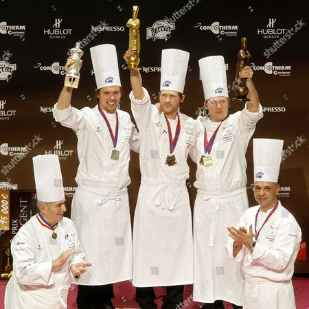 """Rasmus Kofoed, Tommy Myllymaki, Gunnar Hvarnes Rasmus Kofoed of Denmark, center, celebrates on the podium after winning the """"Bocuse d'Or"""" (Golden Bocuse) trophy, at the 13th World Cuisine contest, in Lyon, central France, ahead Tommy Myllymaki of Sweden, second left, who finished second, and Gunnar Hvarnes of Norway, second right, who placed third, . Paul Bocuse, left, and his son Jerome Bocuse, right, attend the ceremony. The contest, a sort of world cup of the cuisine, was started in 1987 by Lyon chef Paul Bocuse to reward young international culinary talents"""