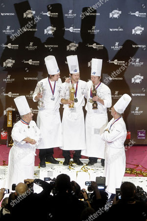 """Rasmus Kofoed, Tommy Myllymaki, Gunnar Hvarnes Rasmus Kofoed of Denmark, center, celebrates on the podium after winning the """"Bocuse d'Or"""" (Golden Bocuse) trophy, at the 13th World Cuisine contest, in Lyon, central France, ahead of Tommy Myllymaki of Sweden, second left, who finished second, and Gunnar Hvarnes of Norway, second right, who placed third, . Paul Bocuse, left, and his son Jerome Bocuse, right, attend the ceremony. The contest, a sort of world cup of the cuisine, was started in 1987 by Lyon chef Paul Bocuse to reward young international culinary talents"""