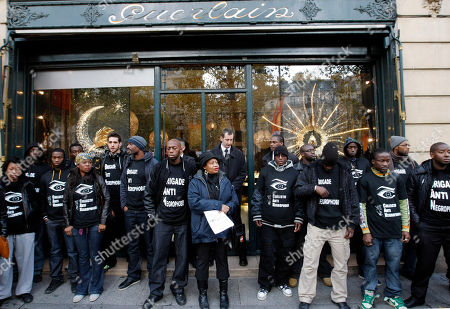 People demonstrate in front of a Guerlain shop in Paris, . French perfumer Jean-Paul Guerlain has caused controversy in France for using a racial epithet on television while discussing the making of his fragrance Samsara. T-shirts read in French, 'Brigade Anti Negro Phobic