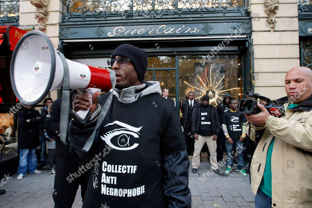 People demonstrate in front of a Guerlain shop in Paris, . French perfumer Jean-Paul Guerlain has caused controversy in France for using a racial epithet on television while discussing the making of his fragrance Samsara. T-shirts read in French, 'Collective Anti Negro Phobic