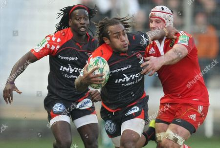 Munster's Denis Leamy, right, challenges Toulon's Paul Sackey, left, and Gabirieli Lovobalavu during their Heineken European Cup rugby match, in Toulon, southeastern France