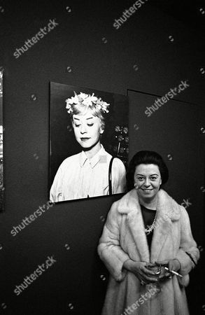 """Italian actress Giulietta Masina smiles while holding a cigarette, in front of a portrait of herself on at the opening of an exhibition of still photographs from her husband's, Italian film director Federico Fellini, film """"Le Notti di Cabiria"""" (Nights of Cabiria) at the City Museum in Munich, Germany"""