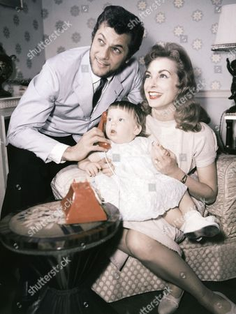 """American actor Tony Curtis, and his wife actress Janet Leigh, pose with their daughter Kelly in London,United Kingdom in June 1957, on route to Norway for the shooting of the movie """"The Vikings"""