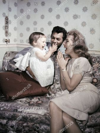 """American Actor Tony Curtis, his wife actress Janet Leigh, and daughter Kelly play together in London, United Kingdom, in June 1957, on route to Norway for the shooting of the movie """"The Vikings"""